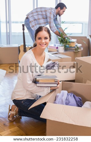 Cute couple unpacking cardboard boxes in their new home - stock photo