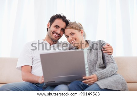 Cute couple using a laptop in their living room - stock photo