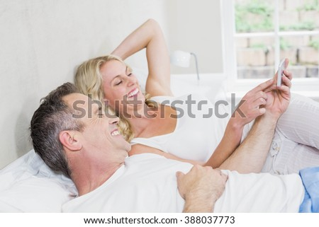 Cute couple using smartphone in bed