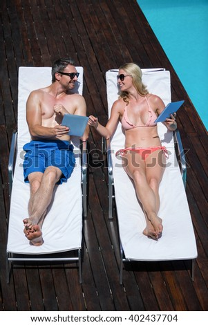 Cute couple using tablet and lying on deckchairs resting next to the pool - stock photo