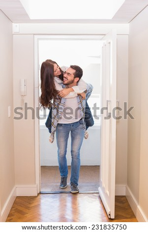 Cute couple walking through the door in their new home - stock photo