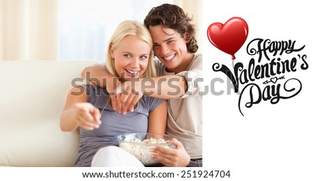 Cute couple watching TV while eating popcorn against cute valentines message - stock photo