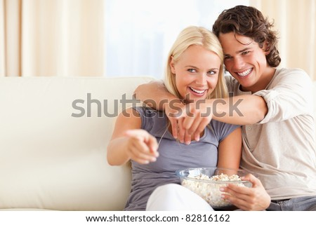 Cute couple watching TV while eating popcorn in their living room - stock photo