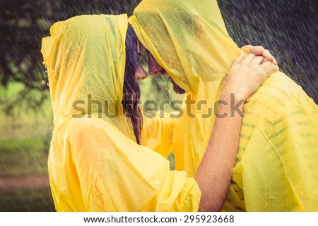 Cute couple wearing protection cape and hugging under the rain in the park - stock photo