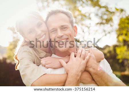 Cute couple with arms around each other outside - stock photo