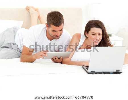 Cute couple working together on their laptop lying on their bed at home