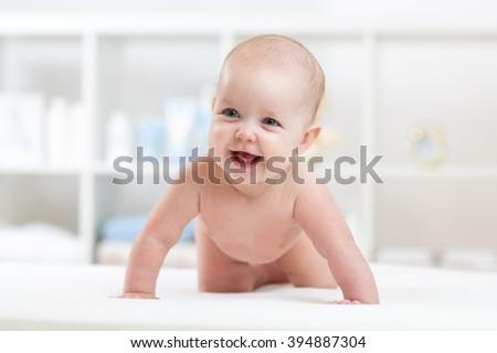 cute crawling baby girl at home - stock photo