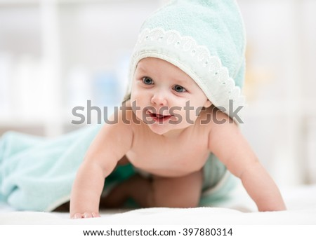 Cute crawling baby under ttowel after bath - stock photo