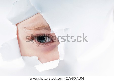 Cute curious baby girl looking through paper hole  - stock photo