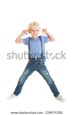 Cute curly blond boy wearing a blue shirt, suspenders, jeans and sneakers, jumping and waving his hands. Studio shot, isolated on white background. - stock photo