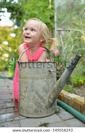 Cute curly girl watering flowers in the garden