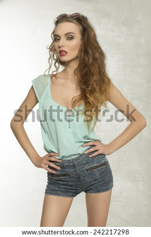 cute curly girl with perfect body posing with denim shorts, blue shirt and vintage sunglasses on the head. Looking in camera with charming expression  - stock photo