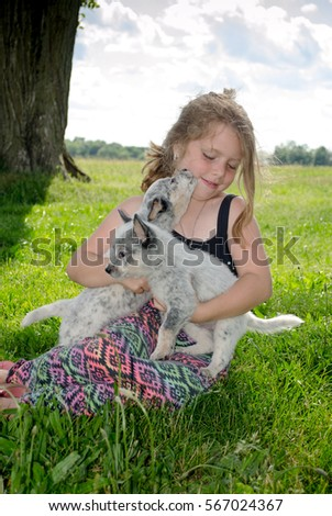 cute curly haired girl wrestles with new puppies in a green field