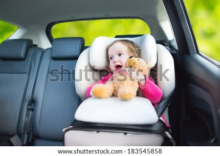 Cute curly laughing and talking toddler girl playing with a toy bear enjoying a family vacation car ride in a modern safe vehicle sitting in a baby seat with belt having fun watching out of the window - stock photo