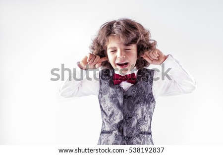 Cute curly little boy screaming with his eyes closed and ears. Close-up. Gray background.
