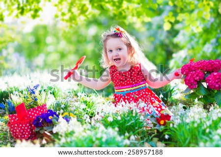 Cute curly little girl in a red summer dress working in the garden watering first spring flowers on a sunny warm day - stock photo