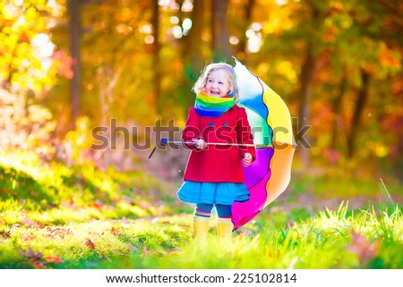 Cute curly little girl wearing a warm red coat and rain boots playing with colorful umbrella enjoying a sunny autumn day in a beautiful fall park - stock photo