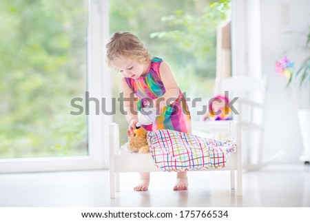 Cute curly toddler girl feeding her toy bear in a white crib playing in a sunny bedroom with big garden view windows - stock photo