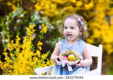 Cute curly toddler girl in a blue dress enjoying Easter egg hunt in the garden with blooming yellow forsythia flowers sitting on a white chair holding a basket with colorful eggs and a pink bow - stock photo