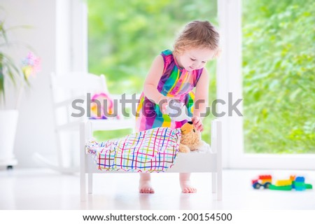 Cute curly toddler girl in a colorful dress feeding her toy bear in a white crib playing in a sunny bedroom with big garden view windows  - stock photo