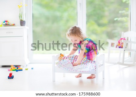 Cute curly toddler girl playing with her bear in a sunny room with big garden view windows - stock photo