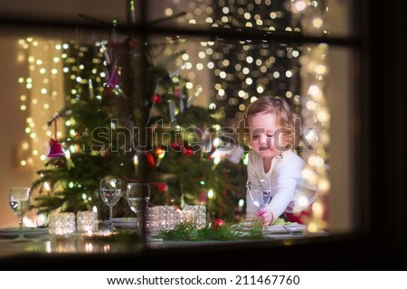 Cute curly toddler girl standing at a Christmas dinner table settling the dishes preparing to celebrate Xmas Eve, view through a window from outside into a decorated dining room with tree and lights - stock photo