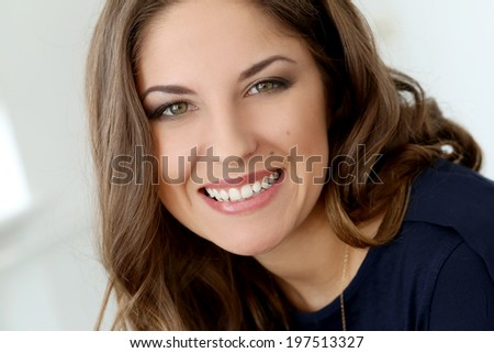 Cute, curly woman with wide smile