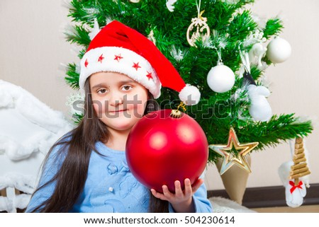 Cute dark-haired girl with a big red Christmas-tree ball
