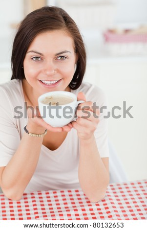 Cute dark-haired woman having a coffee in her kitchen
