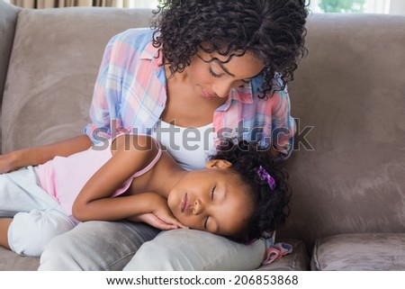 Cute daughter sleeping across mothers lap on the sofa at home in the living room - stock photo