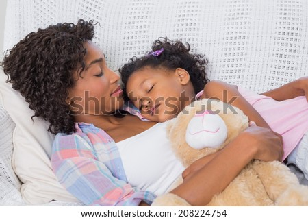 Cute daughter sleeping with mother on the sofa at home in the living room - stock photo