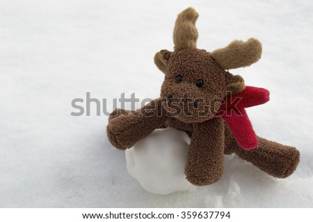 Cute deer with red scarf - christmas toy sits in the snow and leans on a snowball winter greeting card new year january valentines day valentine koronczi stag 2016 background old vintage love retro  - stock photo