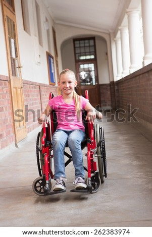 Cute disabled pupil smiling at camera in hall at the elementary school - stock photo
