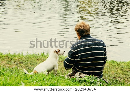 Cute dog funny Jack-Russell-terrier nature with man sitting near water together - stock photo