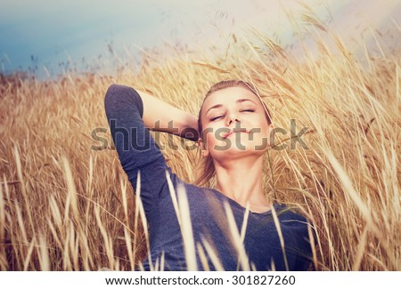 Cute dreamy girl on golden ripe wheat field, lying down with closed eyes and enjoying beautiful mild sunset light and autumn nature - stock photo