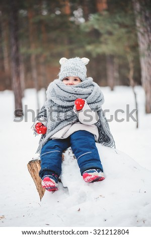 cute dreamy toddler girl in oversize knitted scarf and red gloves on the walk in winter snowy forest - stock photo