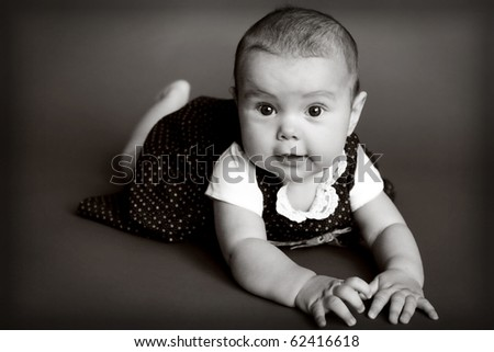 Cute dressed up baby girl laying on her tummy - stock photo