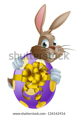 Cute Easter bunny cartoon character holding onto and peeking round a painted chocolate Easter egg