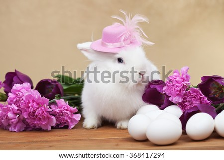 Cute easter rabbit with spring flowers and white eggs - on golden background