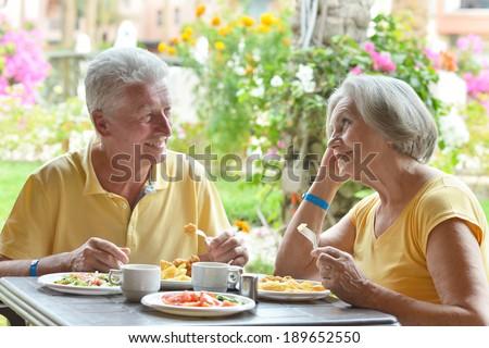 Cute elder couple eating breakfast  in summer outdoors - stock photo