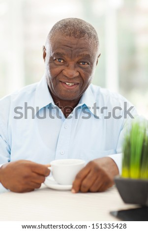 cute elderly african american man having coffee at home - stock photo