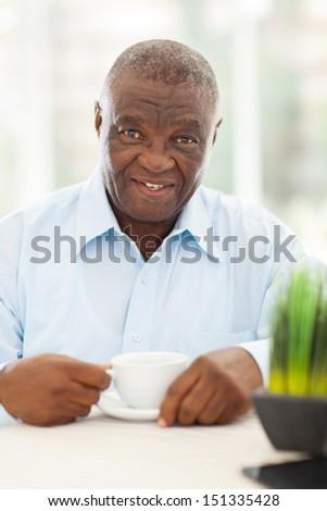 cute elderly african american man having coffee at home - stock photo