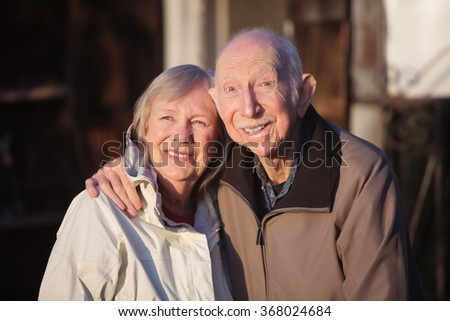 Cute elderly Caucasian couple in jackets smiling outdoors - stock photo