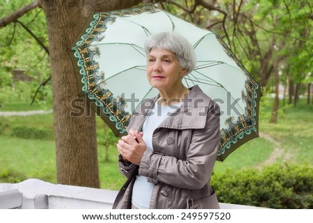 cute elderly woman senior with an umbrella on the beautiful white verandah in the park