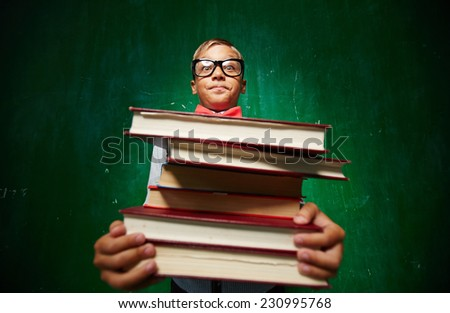 Cute elementary pupil holding heavy stack of textbooks - stock photo