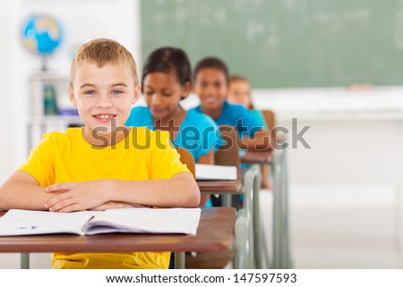 cute elementary schoolboy with classmates in classroom