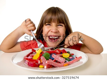 cute European female child smiling happy eating candy like crazy with fork and knife in sugar abuse , unhealthy sweet nutrition concept , children candy addiction and kids  dental care - stock photo