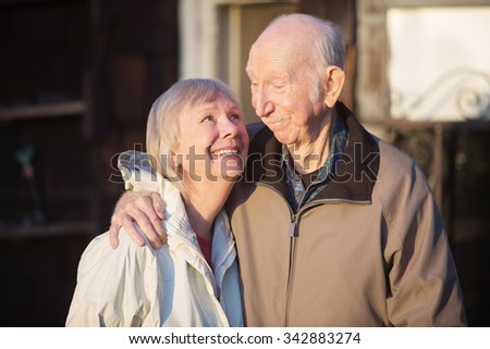 Cute European senior couple outdoors looking at each other - stock photo