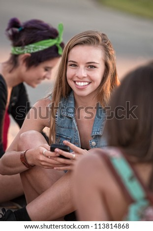 Cute European teenage girl sitting on ground with phone - stock photo