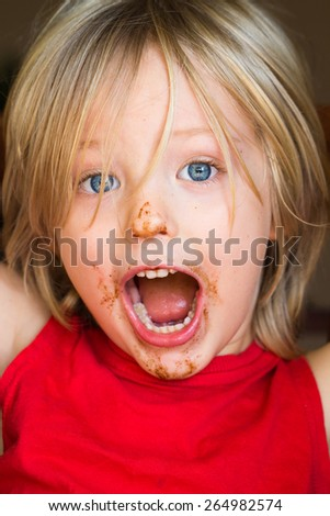 Cute, excited, shouting child with chocolate over face - stock photo